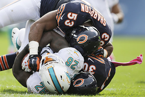 Miami Dolphins running back Lamar Miller (26) is tackled by Chicago Bears cornerback Demontre Hurst (30) and linebacker Darryl Sharpton (53) during the first half of an NFL football game Sunday, Oct. 19, 2014 in Chicago. (AP Photo/Nam Y. Huh)